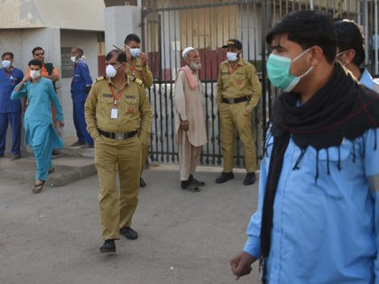 Security personnel (C) and hospital staff wearing facemasks stand outside an hospital entrance in Karachi on February 17, 2020, after agasleakkilledfive people and sickened dozens of others in a coastal residential area in Pakistan's port city ofKarachi. (Photo by Rizwan TABASSUM / AFP) (Photo by RIZWAN TABASSUM/AFP via Getty Images)