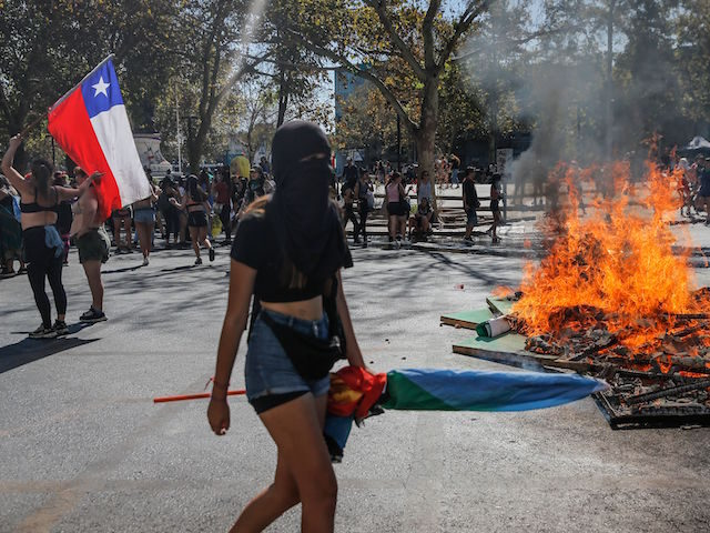 A woman walks past a fire set by demonstrators during clashes with riot police which erupted during a march on International Women's Day, in Santiago on March 8, 2020. - Protests, strikes and studies -- people around the globe are taking action to mark International Women's Day and to push …