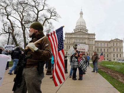 "People take part in a protest for ""Michiganders Against Excessive Quarantine"" at the Michigan State Capitol in Lansing, Michigan on April 15, 2020. - The group is upset with Michigan Governor Gretchen Whitmer's(D-MI) expanded the states stay-at-home order to contain the spread of the coronavirus. (Photo by JEFF KOWALSKY / …"