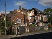 A man walks past a derelict house in Moss Side in Manchester, north-west England on May 11, 2020, as life in Britain continues during the nationwide lockdown due to the novel coronavirus pandemic. (Photo by Oli SCARFF / AFP) (Photo by OLI SCARFF/AFP via Getty Images)