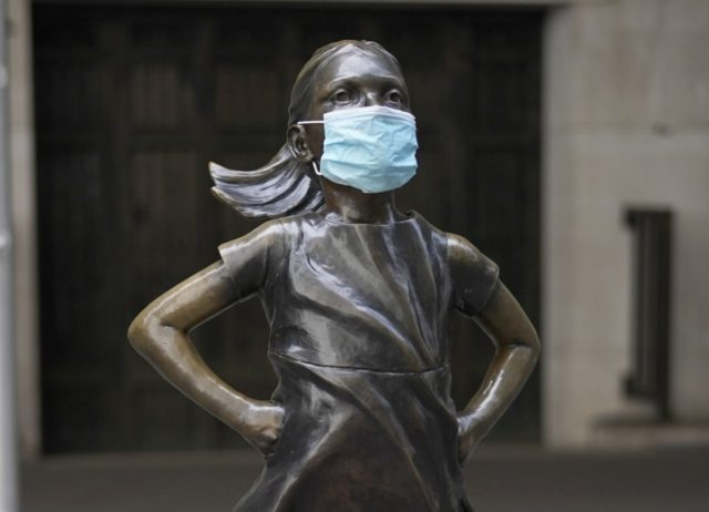 Fearless Girl, a bronze sculpture by Kristen Visbalthe, with a PPE mask on in front of the New York Stock Exchange in the Wall Street Financial District of Manhattan New York May 19, 2020. (Photo by TIMOTHY A. CLARY / AFP) /