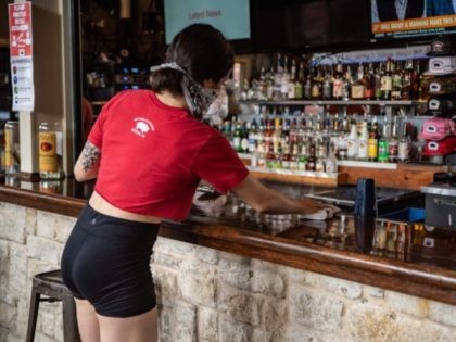A bartender cleans the counter at a bar in Austin, Texas on Friday, May 22, 2020. - Austin allowed bingo halls, bars and bowling alleys to reopen on Friday May 22. (Photo by Sergio Flores / AFP) (Photo by SERGIO FLORES/AFP via Getty Images)