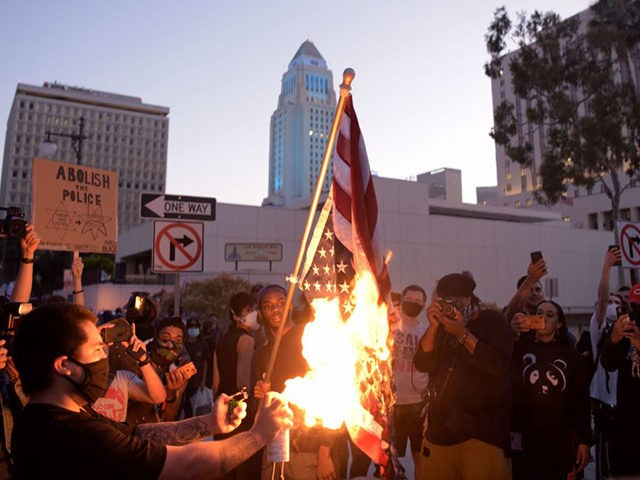 TOPSHOT - A man burns an upsidedown US flag as protesters gather in downtown Los Angeles on May 27, 2020 to demonstrate after George Floyd, an unarmed black man, died while being arrested by a police officer in Minneapolis who pinned him to the ground with his knee. - Outrage …