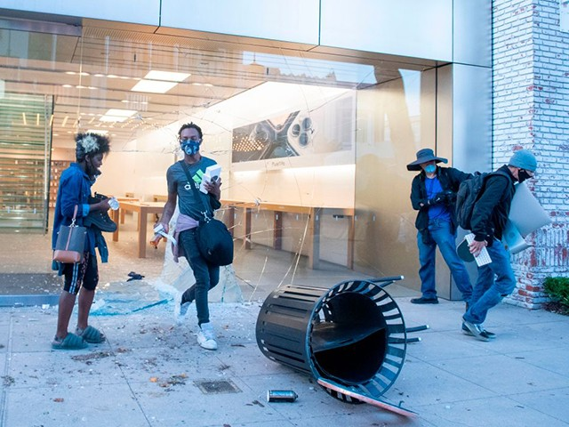 """People are seen looting the Apple store at the Grove shopping center in the Fairfax District of Los Angeles on May 30, 2020 following a protest against the death of George Floyd, an unarmed black man who died while while being arrested and pinned to the ground by the knee of a Minneapolis police officer. - Clashes broke out and major cities imposed curfews as America began another night of unrest Saturday with angry demonstrators ignoring warnings from President Donald Trump that his government would stop violent protests over police brutality """"cold."""" (Photo by VALERIE MACON / AFP) (Photo by VALERIE MACON/AFP via Getty Images)"""