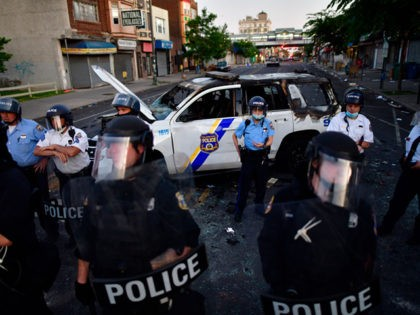 PHILADELPHIA, PA - MAY 31: Police create a barrier in front of a damaged police vehicle during widespread unrest following the death of George Floyd on May 31, 2020 in Philadelphia, Pennsylvania. Protests have erupted all across the country in response to the death of George Floyd while in police …