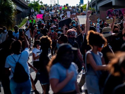 Protesters march during a rally in response to the recent death of George Floyd, an unarmed black man who died while in police custody in Minneapolis, in Miami, Florida on May 31, 2020. - Thousands of National Guard troops patrolled major US cities after five consecutive nights of protests over …