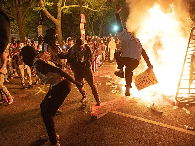 TOPSHOT - Protesters jump on a street sign near a burning barricade during a demonstration against the death of George Floyd near the White House on May 31, 2020 in Washington, DC. - Thousands of National Guard troops patrolled major US cities after five consecutive nights of protests over racism …