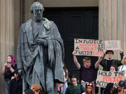 Protesters hold placards next to the statue of 19th century British Prime Minister Benjamin Disraeli outside St George's Hall in Liverpool, northwest England, on June 2, 2020, during demonstration after George Floyd, an unarmed black man who died after a police officer knelt on his neck during an arrest in …