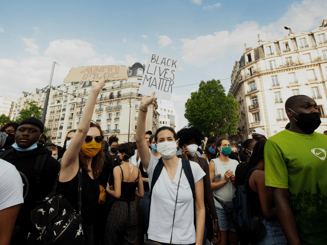 Protesters demonstrate in front of Paris courthouse against police violence on June 2, 2020. - Some 20,000 people defied a ban in Paris on Tuesday to protest the 2016 death of a young black man named Adama Traore in French police custody, some clashing with police and using slogans like …