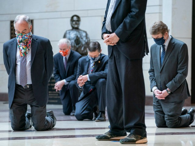WASHINGTON, DC - JUNE 04: Senate Democrats, including Sen. Tim Kaine (D-VA), Sen. Michael Bennet (D-CO), take a knee as they participate in a moment of silence to honor George Floyd and the Black Lives Matter movement in Emancipation Hall of the U.S. Capitol on June 4, 2020 in Washington, …