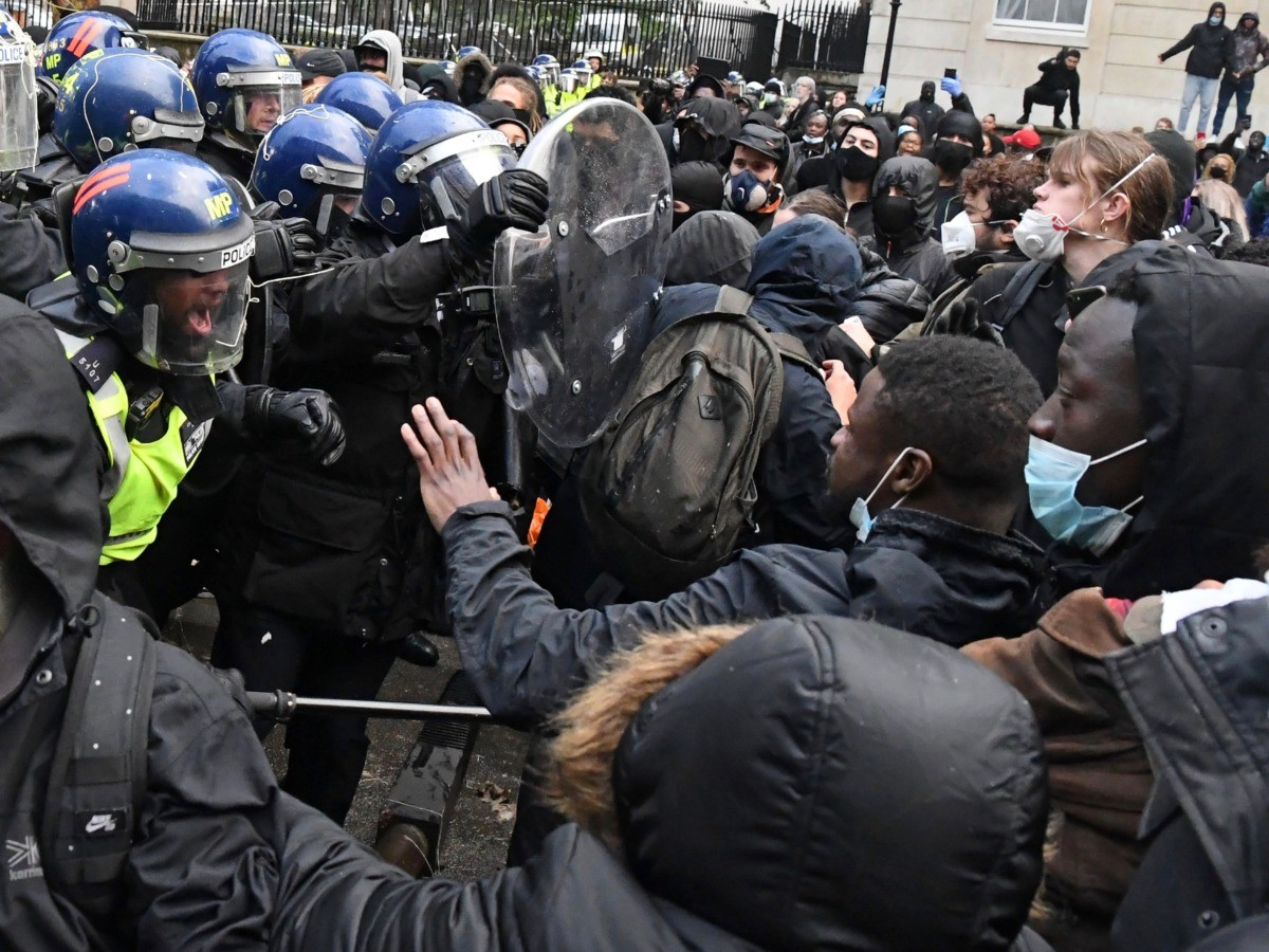 Protestors scuffle with Police officers in riot gear near Downing Street, in central London on June 6, 2020, during a demonstration organised to show solidarity with the Black Lives Matter movement in the wake of the killing of George Floyd, an unarmed black man who died after a police officer knelt on his neck in Minneapolis. - The United States braced Friday for massive weekend protests against racism and police brutality, as outrage soared over the latest law enforcement abuses against demonstrators that were caught on camera. With protests over last week's police killing of George Floyd, an unarmed black man, surging into a second weekend, President Donald Trump sparked fresh controversy by saying it was a