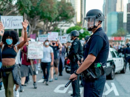 Protesters march past LAPD officers during a demonstration over the death of George Floyd while in Minneapolis Police custody, in downtown Los Angeles, California, June 6, 2020. - Demonstrations are being held across the US following the death of George Floyd on May 25, 2020, while being arrested in Minneapolis, …