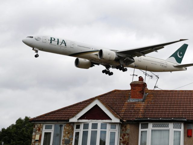A Pakistan International Airlines Boeing 777 comes in over houses, to land at Heathrow airport in west London as the UK government's planned 14-day quarantine for international arrivals to limit the spread of Covid-19 starts on June 8, 2020. (Photo by Adrian DENNIS / AFP) (Photo by ADRIAN DENNIS/AFP via …