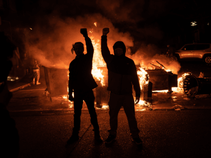 Demonstrators raise their fists as a fire burns in the street after clashes with law enforcement near the Seattle Police Departments East Precinct shortly after midnight on June 8, 2020 in Seattle, Washington. Earlier in the evening, a suspect drove into the crowd of protesters and shot one person, which …
