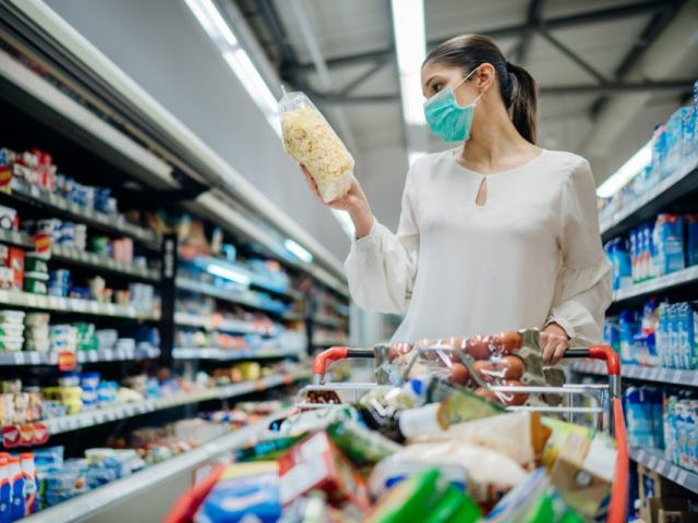 Young person with protective face mask buying groceries.