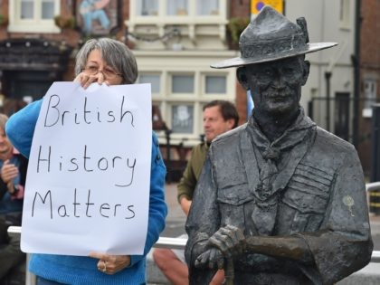 "A woman holds a placards reading ""British History Matters"" alongside a statue of Robert Baden-Powell, the founder of the Scout movement, on the quayside in Bournemouth, southern England, on June 11, 2020, after the council said it would remove the statue. - Authorities in the seaside town of Bournemouth were …"