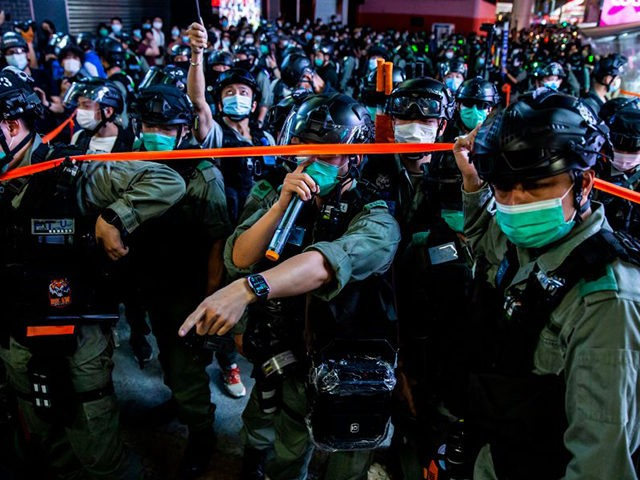 TOPSHOT - Police conduct a clearing operation as protesters gathered in the Mong Kok district of Hong Kong on June 12, 2020. - Thousands of Hong Kongers sang a protest anthem and chanted slogans across the city on June 12 as they marked the one-year anniversary of major clashes between …