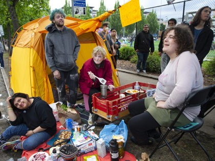 SEATTLE, WA - JUNE 12: A group of friends (L-R) Azzy Grey, Klaire Lee, Onyx Nelson and Samara Isley make food they offer for free with produce they got for free in an area dubbed the Capitol Hill Autonomous Zone (CHAZ) on June 12, 2020 in Seattle, Washington. The area …