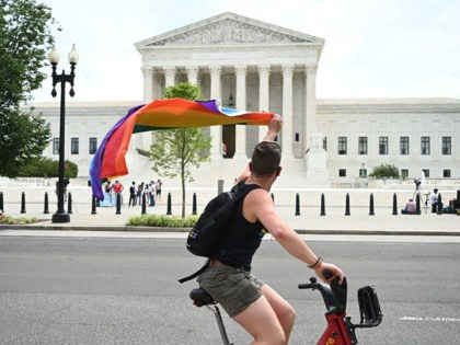 A man waves a rainbow flag as he rides by the US Supreme Court that released a decision that says federal law protects LGBTQ workers from discrimination on June 15, 2020 in Washington,DC. - The US top court has ruled it illegal to fire workers based on sexual orientation. (Photo …