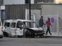 People walk past a burnt van in the Gresilles area of Dijon, eastern France, on June 15, 2020, as new tensions flared in the city after it was rocked by a weekend of unrest blamed on Chechens seeking vengeance for an assault on a teenager. - Police sources said the …