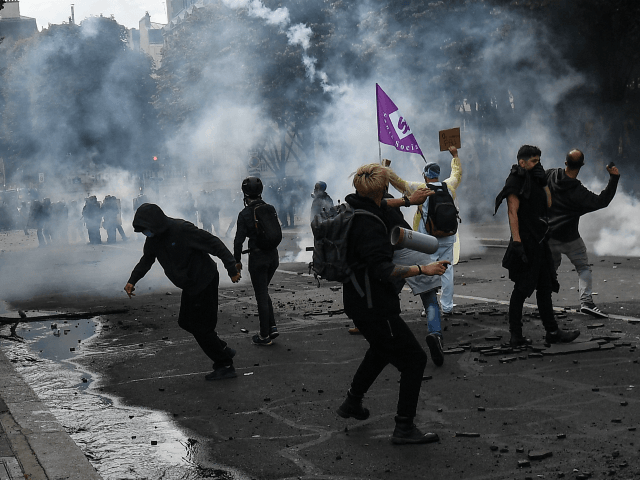 TOPSHOT - Protesters clash with police on the Invalides esplanade during a demonstration in Paris, on June 16, 2020, as part of a nationwide day of protests to demand better working conditions for health workers. (Photo by Alain JOCARD / AFP) (Photo by ALAIN JOCARD/AFP via Getty Images)