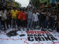 TOPSHOT - Congress party supporters shout slogans as they gather around a flag displaying the country and flag of China along with an inscription reading 'Boycott Made in China' before burning them during an anti-China demonstration in Kolkata on Juane 18, 2020. - India and China agreed on June 17 …
