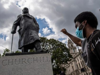 LONDON, ENGLAND - 20 JUNE: A protester raises his fist next to a statue of Winston Churchill in Parliament Square during a Black Lives Matter demonstration on June 20, 2020 in London, United Kingdom. Black Lives Matter protests are continuing across the UK following the death of African American George …