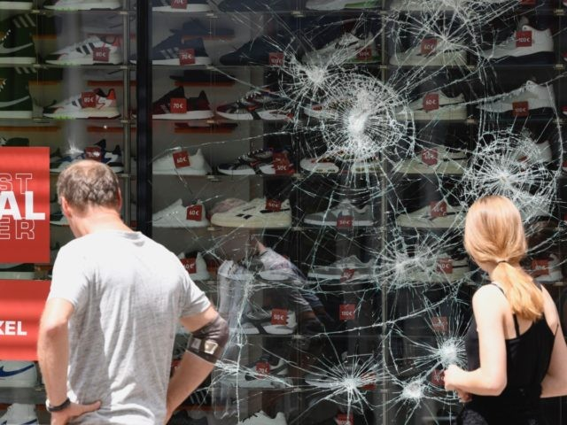 People look on a destroyed shop window of a shoe store in Stuttgart, southern Germany on June 21, 2020. - Hundreds of people ran riot in Stuttgart's city centre in the early hours of Sunday, June 21, 2020, throwing stones and bottles at police and plundering stores after smashing shop …