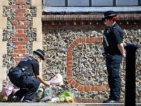 TOPSHOT - A police officers lays flowers, given by a member of the public, at an entrance of Forbury Gardens park in Reading, west of London, on June 22, 2020, the scene of the June 20 stabbing spree. - A suspect held on suspicion of stabbing three people to death …