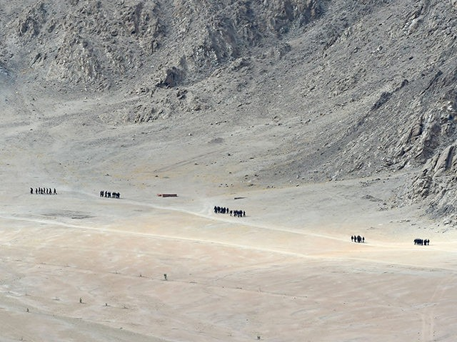 Indian soldiers walk at the foothills of a mountain range near Leh, the joint capital of the union territory of Ladakh, on June 25, 2020. - Indian fighter jets roared over a flashpoint Himalayan region on June 24 as part of a show of strength following what military sources say …