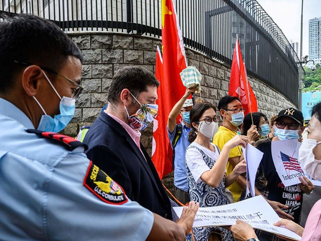 A US consulate representative (centre L) comes out to collect a letter from a group of pro-China activists holding placards and flags outside the US Consulate General in Hong Kong on June 26, 2020, a day after the US Senate unanimously approved a bill that would lay out sanctions on …