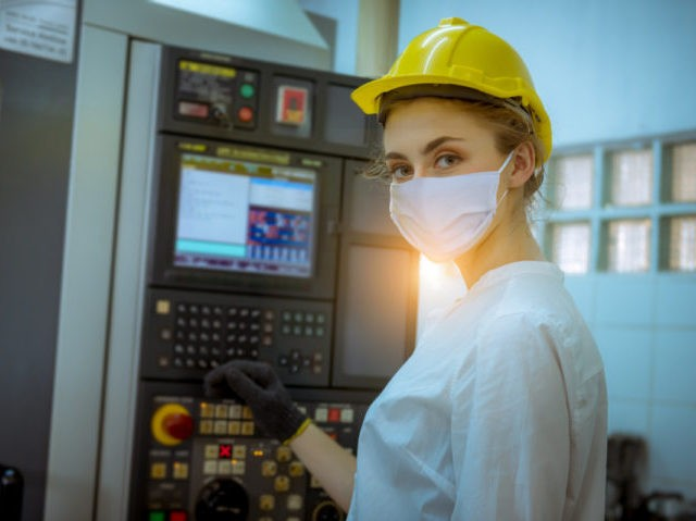 Portrait woman worker under inspection and checking production process on factory station by wearing safety mask face to protect for pollution and virus in factory.