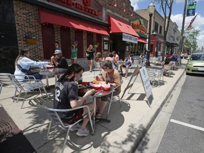 "LAGRANGE, ILLINOIS - MAY 29: Diners eat lunch on the sidewalk in front of Casa Margarita restaurant on May 29, 2020 in LaGrange, Illinois. Phase 3 of Illinois governor J.B. Pritzker's ""Restore Illinois"" plan began today with limited reopening's of some businesses as a step toward restoring normal life during …"