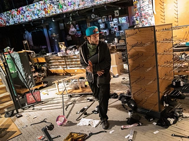 NEW YORK, NEW YORK - JUNE 1: A looter grabs merchandise during a night of protests and vandalism over the death of George Floyd on June 1, 2020 in New York City. Thousands of protesters took to the streets throughout the city on Monday to express their anger at police …
