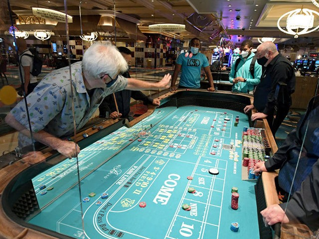 LAS VEGAS, NEVADA - JUNE 04: Guests play craps on a table with plexiglass safety shields at Bellagio Resort & Casino on the Las Vegas Strip after the property opened for the first time since being closed on March 17 because of the coronavirus (COVID-19) pandemic on June 4, 2020 …