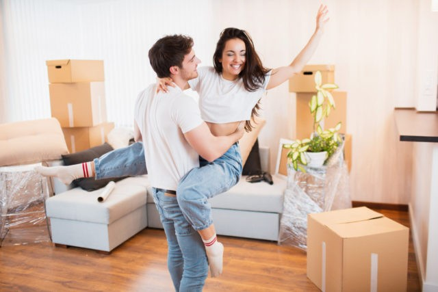 Overjoyed young couple dance in living room near cardboard boxes entertain on moving day,
