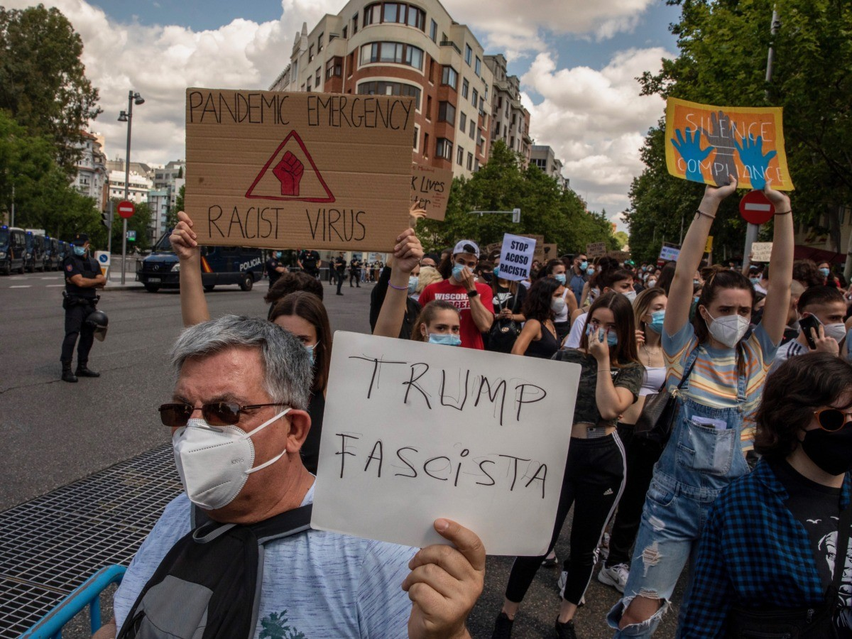 MADRID, SPAIN - JUNE 07: Demonstrators wear protective masks as they hold placards reading (L-R) 'Pandemic Emergency. Racist Virus.', 'Trump Fascist' and 'Silence Compliance' during a Black Lives Matter protest following the death of George Floyd outside the United States Embassy on June 07, 2020 in Madrid, Spain.The death of an African-American man, George Floyd, while in the custody of Minneapolis police has sparked protests across the United States, as well as demonstrations of solidarity in many countries around the world. (Photo by Pablo Blazquez Dominguez/Getty Images)