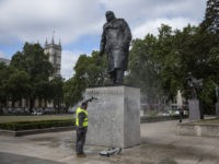 LONDON, ENGLAND - JUNE 08: A worker cleans the Churchill statue in Parliament Square that had been spray painted with the words 'was a racist' on June 08, 2020 in London, England. Outside the Houses of Parliament, the statue of former Prime Minister Winston Churchill was spray-painted with the words …