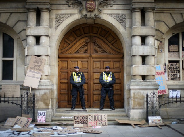 OXFORD, ENGLAND - JUNE 09: Police officers stand guard outside University of Oxford's Oriel College during a protest by the Rhodes Must Fall campaign on June 09, 2020 in Oxford, England. The Rhodes Must Fall campaign protests outside University of Oxford's Oriel College where a statue of imperialist Cecil John …