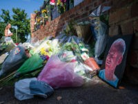 WOKINGHAM, ENGLAND - JUNE 22: A painted portrait is seen among the flowers as students pay their respects to the murdered school teacher James Furlong outside The Holt School, on June 22, 2020 in Wokingham, England. Khairi Saadallah, a 25-year-old refugee from Libya, was arrested on Saturday evening suspected of …