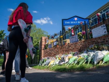 WOKINGHAM, ENGLAND - JUNE 22: A girl holds her skateboard as students lay flowers and pay their respects to the murdered school teacher James Furlong outside The Holt School, on June 22, 2020 in Wokingham, England. Khairi Saadallah, a 25-year-old refugee from Libya, was arrested on Saturday evening suspected of …