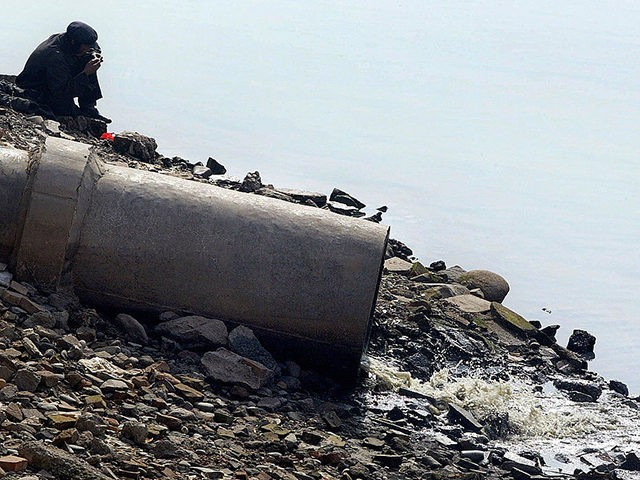 LANZHOU, CHINA: A man sits by the banks of the Yellow River beside a sewage pipe emitting raw sewage, 19 February 2003 in Lanzhou, in northwest China's Gansu province. Rampant overuse of water coupled with heavy silting and pollution were threatening the vitality of China's historic Yellow River, according to …