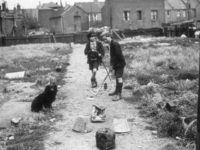 Two London slum boys playing golf on a home made course, consisting of old buckets. (Photo by Hulton Archive/Getty Images)