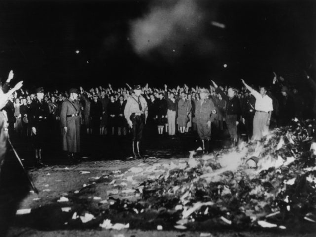 May 1933: German soldiers and civilians give the Nazi salute as thousands of books smoulder during one of the mass book-burnings implemented throughout the country to destroy non-Aryan publications. (Photo by Keystone/Getty Images)