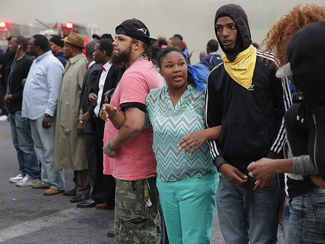 BALTIMORE, MD - APRIL 27: Baltimore residents lock arms and form a line opposing police during violent protests at the corner of Pennsylvania and North avenues following the funeral of Freddie Gray April 27, 2015 in Baltimore, Maryland. Gray, 25, who was arrested for possessing a switch blade knife April …