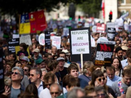 "Demonstrators hold placards as the take part in a pro-refugee rally in central London on September 12, 2015. Tens of thousands of Europeans rallied urging solidarity with the huge numbers of refugees entering the continent, as Hungary's populist premier said leaders were ""in a dream world"" about the dangers posed …"