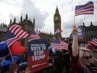 """Activists wave US flags as they ride on a """"Stop Trump"""" battle bus as they approach the Houses of Parliament in London on September 21, 2016 in a campaign run by campaign group Avaaz to mobilise US expatriots in the UK to register to vote in the US presidential election. …"""