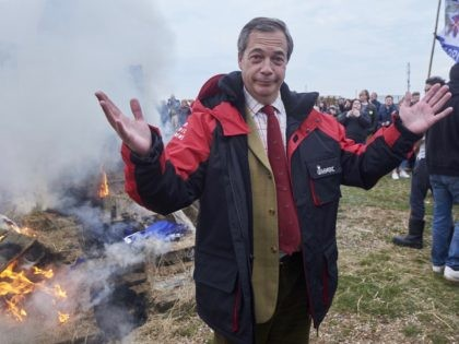 Former UK Indepence Party (UKIP) Leader Nigel Farage (C) stands beside the remains of a small boat on top of a bonfire on the shore during a demonstration in Whitstable, southeast England on April 8, 2018 against the Brexit transition deal that would see Britain continue to adhere to the …