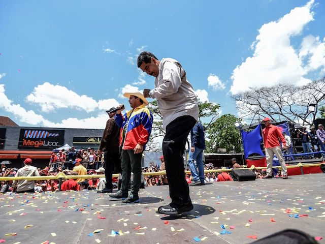Venezuelan President Nicolas Maduro dances during a campaign rally in Charallave, about 65 km from Caracas, on May 15, 2018. - Venezuela holds presidential elections on May 20, in which Maduro is seeking a second six-year term. (Photo by Juan BARRETO / AFP) (Photo credit should read JUAN BARRETO/AFP via …