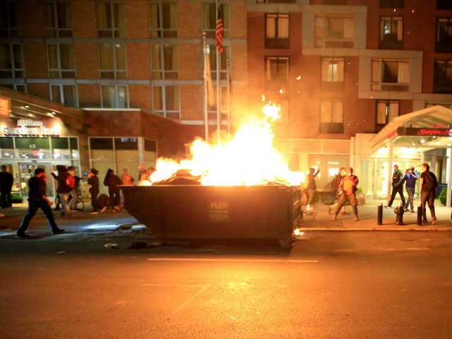 People walk past a dumpster fire in front of the Hampton Inn on west 35th street during a rally in response to the death of George Floyd while in Minneapolis police custody on May 31, 2020 in New York City. Protesters demonstrated for the fourth straight night after video emerged …